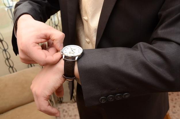 L'homme Regarde La Montre-bracelet En Gros Plan Et Traduit Les Aiguilles De L'horloge Photo Premium