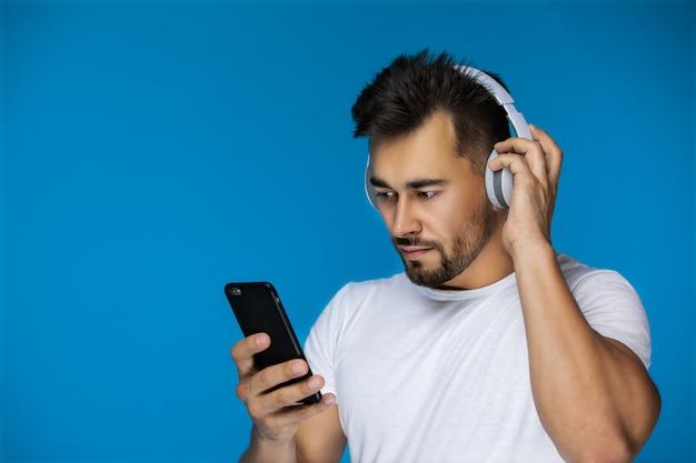 L'homme regarde quelque chose au téléphone et écoute avec les écouteurs