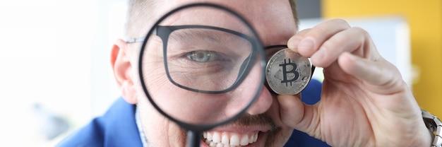L'homme regarde à travers une loupe et tient le bitcoin dans sa main des gains sur la crypto-monnaie