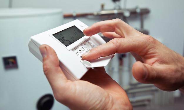 L'homme règle le thermostat dans la chaufferie