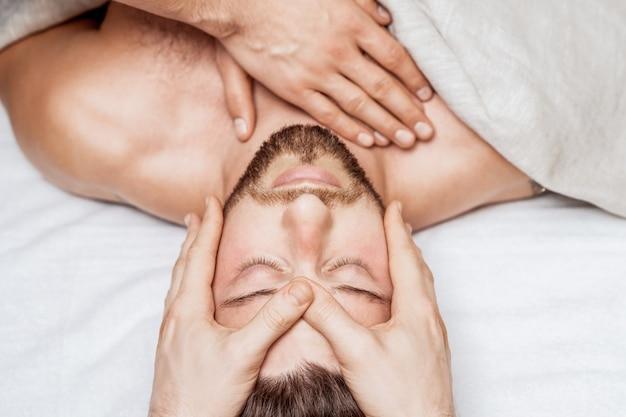 Homme relaxant bénéficiant d'une vue de dessus de massage de la tête.