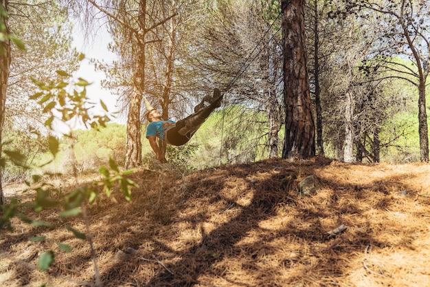 Un homme relaxant dans un hamac en forêt