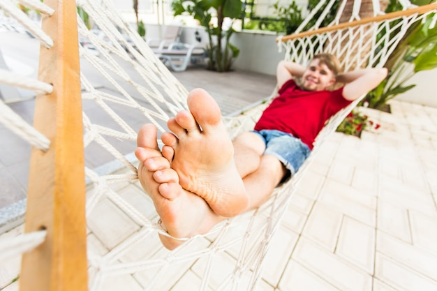 Homme relaxant dans un hamac