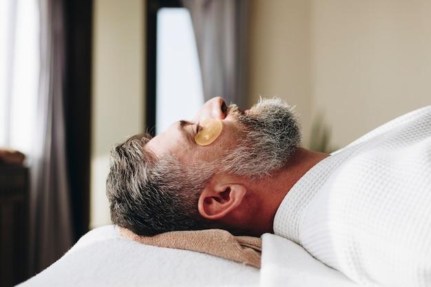 Homme relaxant avec un traitement de masque aux yeux d'or