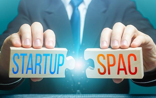 L'homme relie des puzzles avec des mots startup et spac simplification de la procédure de collecte de fonds et de financement pour la fusion de deux sociétés en une nouvelle