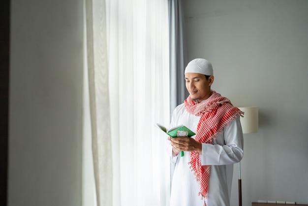 Homme religieux asiatique lecture coran ou coran en se tenant debout à côté de la fenêtre