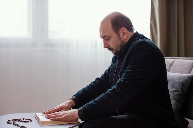 Homme religieux étudiant un livre saint