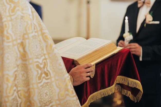 Homme religieux lisant la sainte bible et priant dans l'église avec des bougies allumées, religion et concept de foi