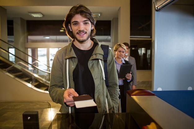 Homme remettant sa carte d'embarquement au comptoir
