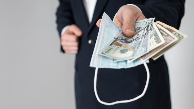 Homme remettant un tas de billets en dollars avec un masque médical