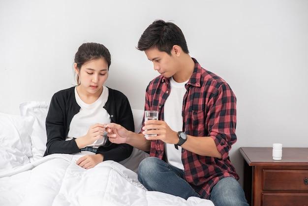 Un homme a remis des médicaments à une femme malade au lit.