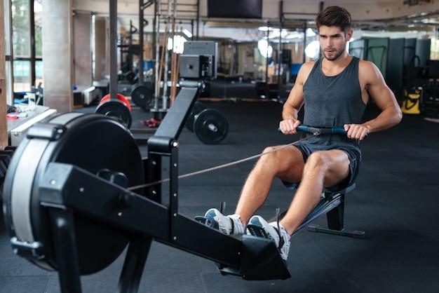 Homme de remise en forme faisant de l'exercice dans la salle de sport et en détournant les yeux. exercice pour vos mains