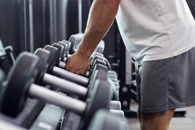 Homme de remise en forme en formation montrant des exercices avec des haltères en salle de gym.