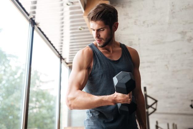 Homme de remise en forme avec haltère dans la salle de gym. détournant les yeux