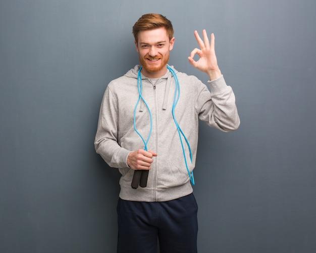 Homme de remise en forme jeune rousse gai et confiant, geste ok. il tient une corde à sauter.