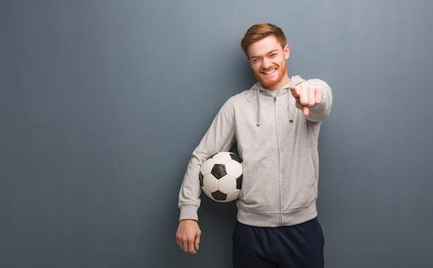 Homme de remise en forme jeune rousse gai et souriant pointant vers l'avant. il tient un ballon de soccer.