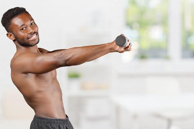 Homme de remise en forme musculaire maigre tonique et déchiré, soulever des poids