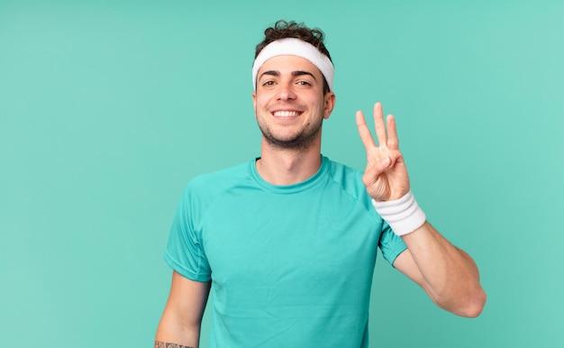 Homme de remise en forme souriant et à l'air sympathique, montrant le numéro trois ou troisième avec la main vers l'avant, compte à rebours