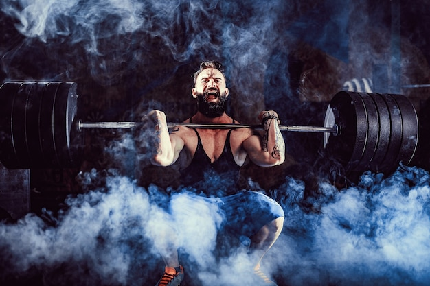 Homme de remise en forme tatoué barbu musclé faisant deadlift une barre au-dessus de sa tête dans un centre de remise en forme moderne.
