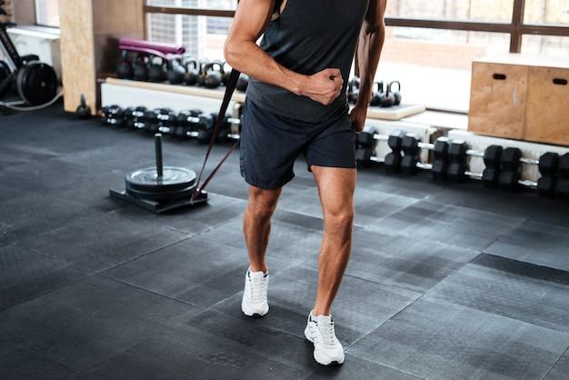 Homme de remise en forme tirant la charge dans la salle de sport. image recadrée