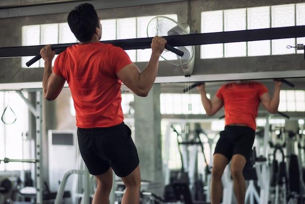 Homme de remise en forme tirant vers le haut de la barre dans la salle de gym