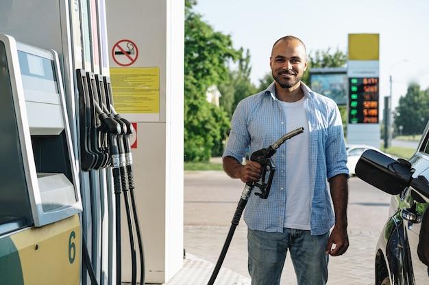 Homme remplissant le carburant d'essence dans la voiture à la station service