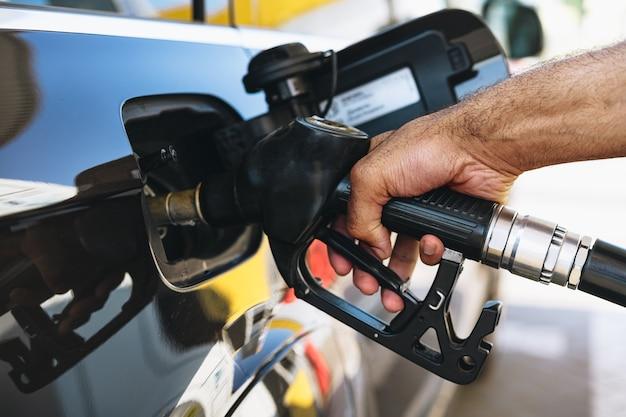 Homme Remplissant Le Carburant D'essence Dans La Voiture à La Station Service Photo Premium
