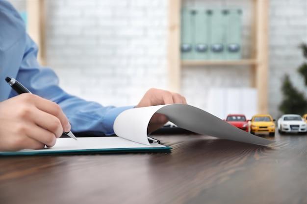Homme remplissant le formulaire d'assurance automobile à table
