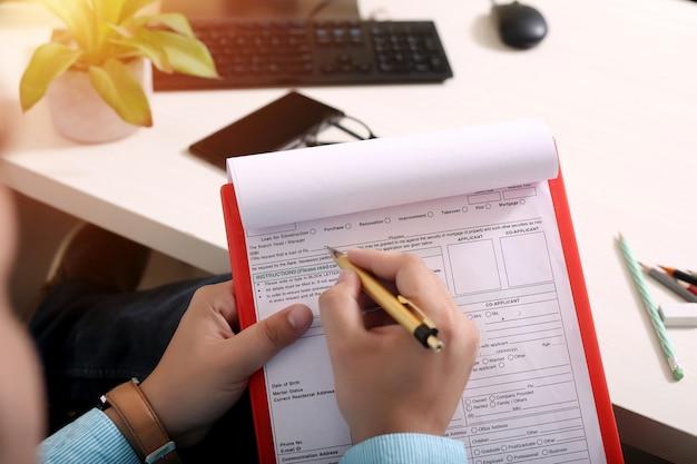 L'homme remplit le formulaire avec un stylo