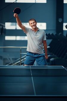 Un homme remporte un match de tennis de table
