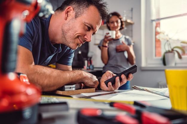 Homme rénovant la cuisine et utilisant un téléphone intelligent