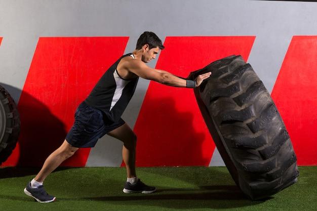 Homme renversant un exercice de gymnase d'entraînement de pneu de tracteur