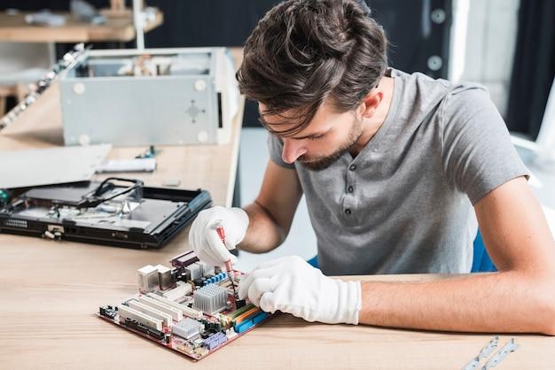 Homme réparant un circuit électronique d'ordinateur