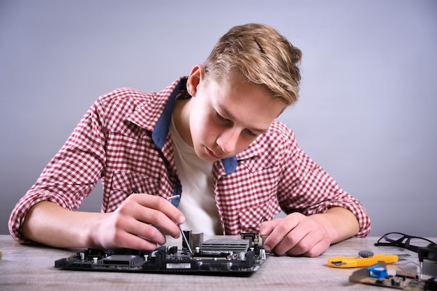 Homme réparant un ordinateur cassé, une carte vidéo, une mémoire ram, un refroidisseur, un processeur, un disque dur.jeune réparateur travaillant avec un tournevis dans un centre de service.