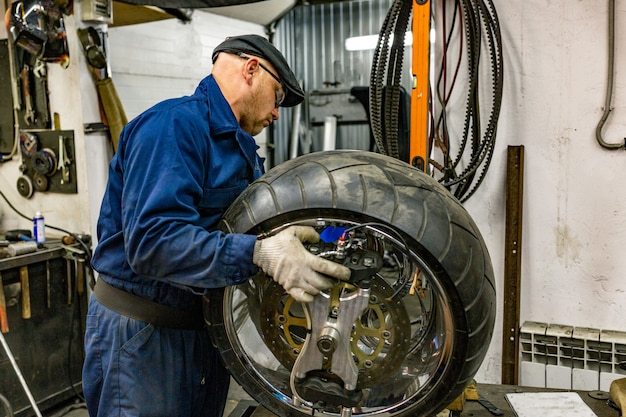 Homme réparant un pneu de moto avec un kit de réparation, kit de réparation de prise de pneu pour pneus sans chambre à air.