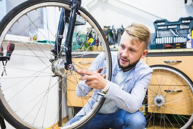 Homme réparant un pneu de vélo avec une clé