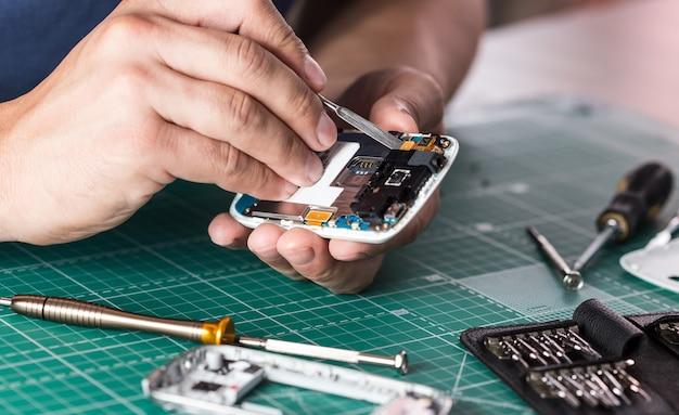 Homme réparant un smartphone cassé, photo en gros plan.