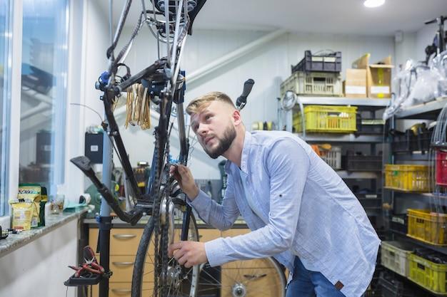 Homme réparant un vélo en atelier
