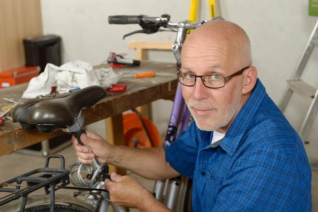 Homme réparant le vélo dans son atelier.
