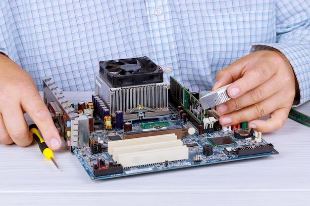 Homme réparateur essaie de réparer en utilisant les outils de l'ordinateur