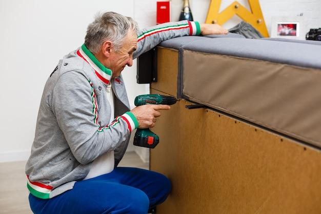Un homme répare un canapé