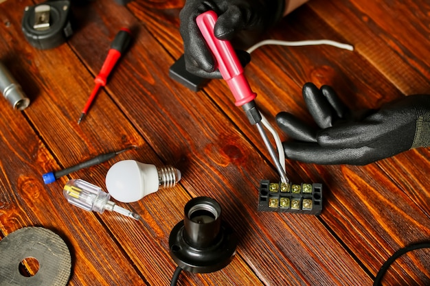 Un homme répare des fils, une lampe. un électricien appelé à la maison, des tournevis, des ampoules, des appareils électriques et des outils. photo de haute qualité