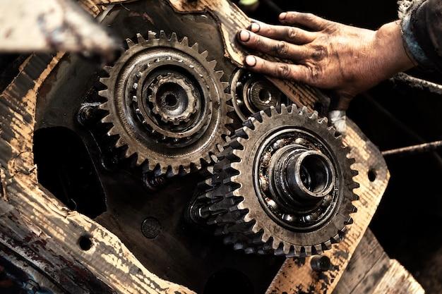 L'homme répare le moteur du tracteur, les machines agricoles. roulement, engrenages, gros plan.