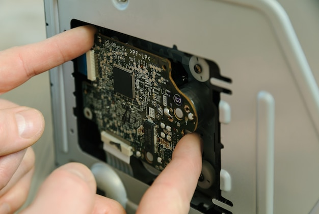 Un homme répare le système musical. il sort une carte électronique.
