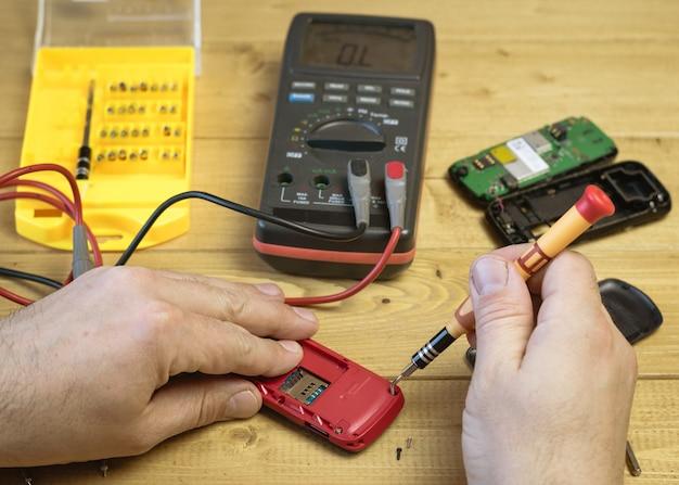 Un homme répare un téléphone portable rouge.