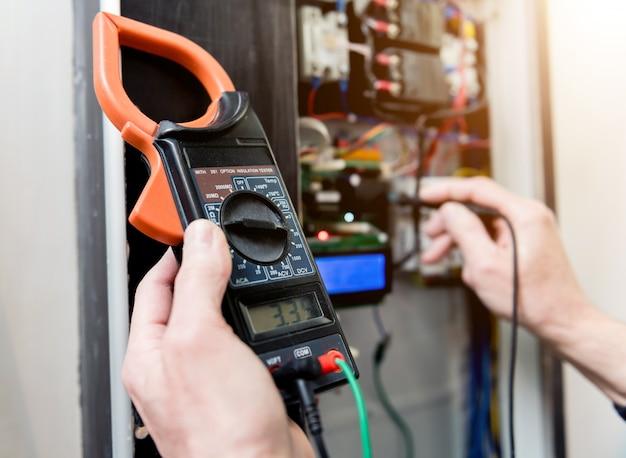 L'homme répare la tension du tableau avec des interrupteurs automatiques.