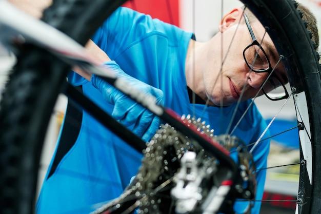 L'homme répare un vélo dans son atelier de petite entreprise