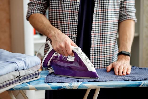 Un homme repasse une chemise sur une planche à repasser avec un fer à repasser les tâches ménagères quotidiennes