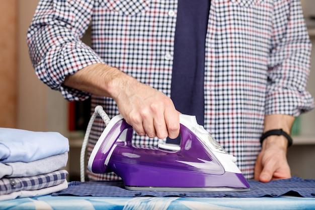 Un homme repasse une chemise sur une planche à repasser avec un fer à repasser. tâches ménagères quotidiennes.