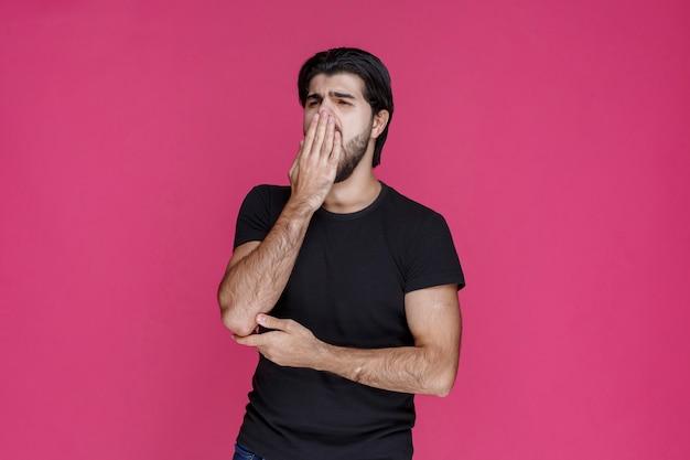 L'homme ressent une mauvaise haleine ou une mauvaise odeur et ferme le nez